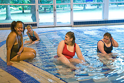 Day Service officer supervising a group of day service users with learning disabilities whilst they are playing in the water at a local swimming pool,