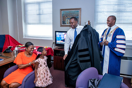 2019 Commencement speaker Kasim Reed and University President Wayne A.I. Frederick speaking to his daughter.