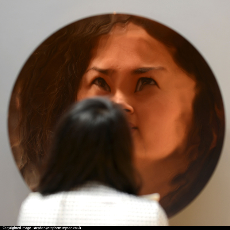 © Licensed to London News Pictures. 14/06/2012. London, UK A woman is reflected in an unnamed sculpture by Anish Kapoor. It is estimated to fetch between 400,000-600,000GBP. Photocall for Sotheby's June Contemporary Art Evening Auction. Photo credit : Stephen Simpson/LNP