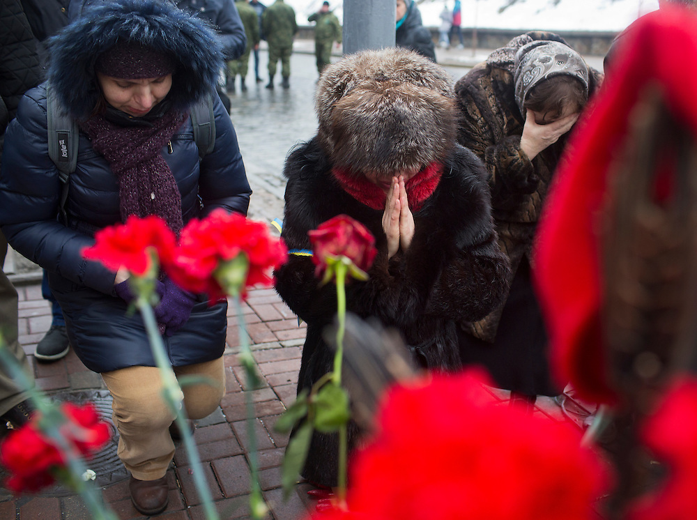 Friends and family of Maksim Shimko pray at the site of his killing on the anniversary of his death on February 20, 2015 in Kyiv, Ukraine.