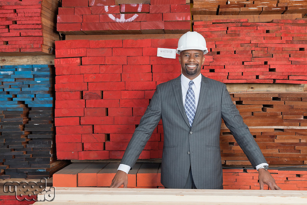 Portrait of happy African American male contractor standing in front of stacked wooden planks
