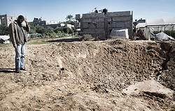 "© Licensed to London News Pictures 29/11/2012.  North Gaza. Eight days after the Israeli missile strikes on Gaza a local farmer looks at the hole left by and air strike.  Ahmed, a tomato farmer has lost his green house which contained a full crop.  ""I was awoken at 2am by something that felt like an earth quake.  We went out as soon as it got light and found our greenhouse had been destroyed.""  Photo credit : Alison Baskerville/LNP"