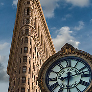 Fifth Avenue Clock in foreground looking up at the  Flatiron Building at 175 Fifth Avenue New York City and is considered to be a groundbreaking skyscraper.<br />