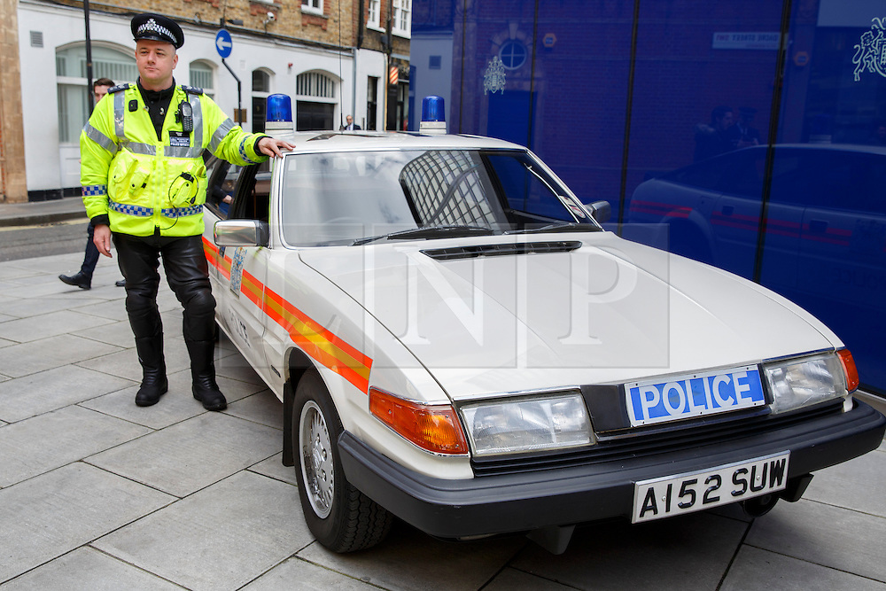 © licensed to London News Pictures. London, UK 26/02/2014. A police officer having his picture taken with a veteran police car outside New Scotland Yard as the Met's iconic cop cars dating back to 1948 taking part at a convoy through central London. Vehicles including the 1948 Wolseley, 1970 Morris, Minor 1000 and the 1973 Special Branch Rover P6 leaving Hampton Traffic Garage for the final time to head up to the Met's Peel Centre in Hendon which will be the new home of the fleet. Photo credit: Tolga Akmen/LNP