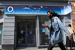 © Licensed to London News Pictures. 07/05/2020. London, UK. A woman holding a mobile phone walks past an O2 store in north London. Virgin Media and O2 are to merge and create a £31 billion media and telecoms giant. The merger is expected to be completed by 2021. Photo credit: Dinendra Haria/LNP