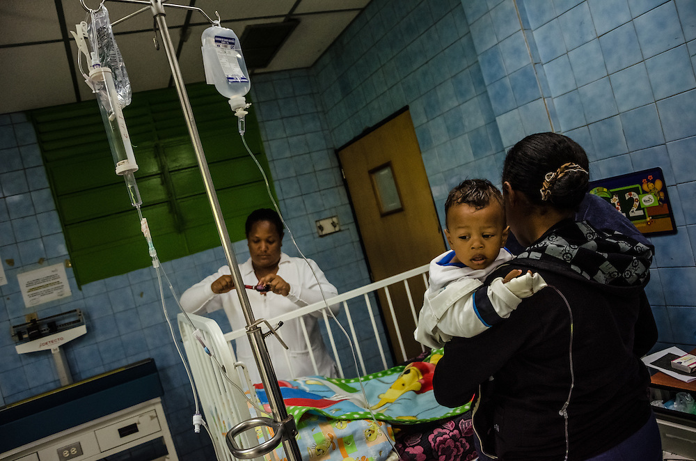 """CARACAS, VENEZUELA - JANUARY 21, 2015: Carmen Ramos, 39, holds her 1-year old son, Isoios Jaimez inside the pediatric ward of a state hospital in the Petare slum in Caracas.  Isoios is suffering from a respiratory infection, and Ms. Ramos has been unable to find the antibiotics prescribed to help him recover. She said her husband and her rotate shifts at the hospital taking care of their son, and waiting in lines at pharmacies in search of his medicines.  She said that doesn't leave them the time to wait in the long lines to find diapers, so they have to buy them on the blackmarket. She recently paid 350 bolivares, over $50 USD at the official rate, for one pack of diapers. """"I can't afford it, but I have to go out and buy [the diapers] wherever I can because he is a small baby,  I can't leave him without diapers"""". Despite being a petro-state with one of the largest oil reserves in the world, basic and advanced medical supplies from gauze and surgical gloves, to heart stints, are difficult to find in hospitals and pharmacies across Venezuela."""