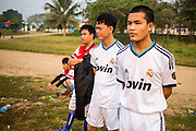 16 MARCH 2013 - ALONG HIGHWAY 13, LAOS: Football (soccer) players watch a game on an improvised field along Highway in Luang Prabang. The paving of Highway 13 from Vientiane to near the Chinese border has changed the way of life in rural Laos. Villagers near Luang Prabang used to have to take unreliable boats that took three hours round trip to get from the homes to the tourist center of Luang Prabang, now they take a 40 minute round trip bus ride. North of Luang Prabang, paving the highway has been an opportunity for China to use Laos as a transshipping point. Chinese merchandise now goes through Laos to Thailand where it's put on Thai trains and taken to the deep water port east of Bangkok. The Chinese have also expanded their economic empire into Laos. Chinese hotels and businesses are common in northern Laos and in some cities, like Oudomxay, are now up to 40% percent. As the roads are paved, more people move away from their traditional homes in the mountains of Laos and crowd the side of the road living off tourists' and truck drivers.   PHOTO BY JACK KURTZ