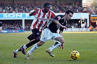 Photo: Leigh Quinnell.<br /> Brentford v Swansea City. Coca Cola League 1.<br /> 26/12/2005. Swanseas Leon Britton finds a way past Brentfords Sam Sodje.