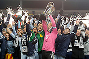 Sporting Kansas City goalkeeper Jimmy Nielsen, center, holds the MLS Cup as he and his teammates celebrate their 2-1 win over Real Salt Lake at the conclusion of the MLS Cup final soccer match in Kansas City, Kan., Saturday, Dec. 7, 2013. (AP Photo/Colin E. Braley)