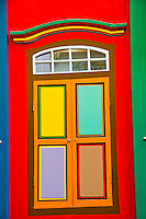 Closeup of a brightly colored  building facade, highlighting window shutters in Little India, Singapore.