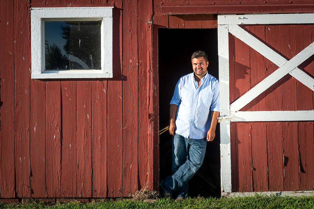 Portrait of a chicken farmer leaning on a red barn door on his farm located on Maryland's Eastern shore.