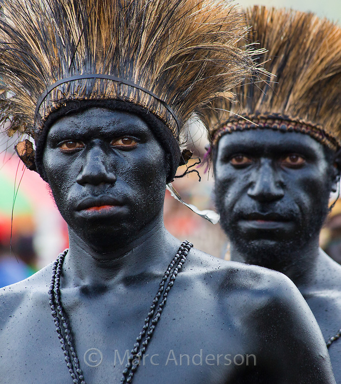 Tribal men painted shiny black and wearing grass headdresses at the Goroka festival in Papua New Guinea.
