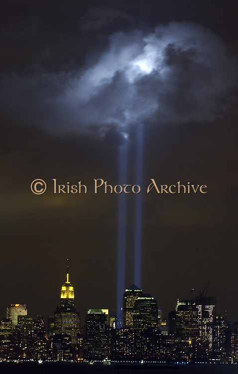 """New York City, N.Y. (Sept. 9, 2004) - As the anniversary of the September 11, 2001 terrorist attack approaches, a test of the Tribute in Light Memorial illuminates a passing cloud above lower Manhattan. The twin towers of light, made-up of 44 searchlights near """"Ground Zero,"""" are meant to represent the fallen twin towers of the World Trade Center. Depending on weather conditions, the columns of light can be seen for at least 20 miles around the trade center complex. U.S. Coast Guard photo"""