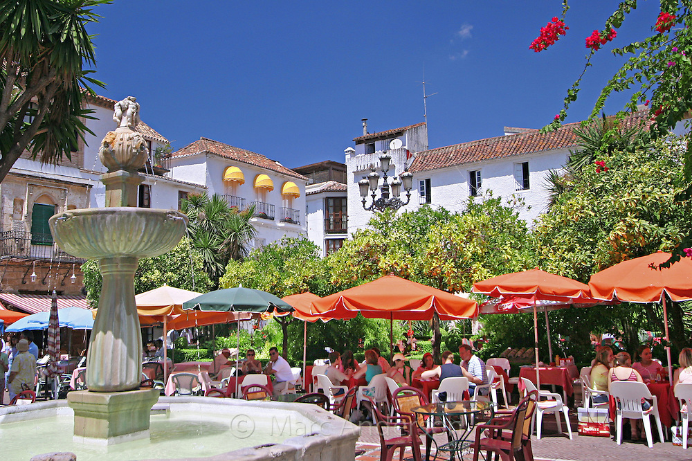 Fountain and people dining, Orange Square (Plaza de los Naranjos), Marbella Old Town, Costa Del Sol, Spain.