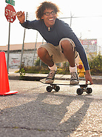 Young man crouching on skateboard in street
