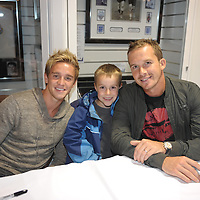 Kevin Davies and Stuart Holden sign autographs for fans during a meet and greet session at the Reebok Stadium in Bolton