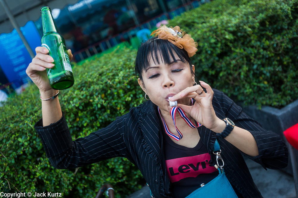 "13 JANUARY 2014 - BANGKOK, THAILAND: A woman drinks a beer and blows a whistle during an anti-government protest in the Asoke intersection of Bangkok. Tens of thousands of Thai anti-government protestors took to the streets of Bangkok Monday to shut down the Thai capitol. The protest was called ""Shutdown Bangkok"" and is expected to last at least a week. The Shutdown Bangkok protest is a continuation of protests that started in early November. There have been shootings almost every night at different protests sites around Bangkok, including two Sunday night, but the protests Monday were peaceful. The malls in Bangkok stayed open Monday but many other businesses closed for the day and mass transit was swamped with both protestors and people who had to use mass transit because the roads were blocked.    PHOTO BY JACK KURTZ"