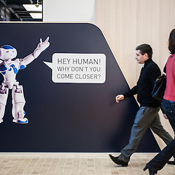 Lyon, France - 19 March 2014: two visitors walk past a banner of NAO Robot at Innorobo 2014, the 4th international trade show on service robotics.