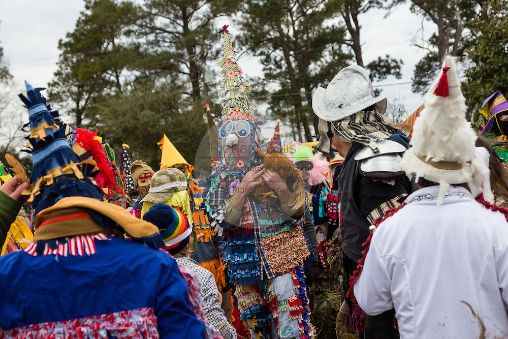 A reveler celebrates catching a live chicken during the Faquetigue Courir de Mardi Gras chicken run on Fat Tuesday February 17, 2015 in Eunice, Louisiana. The traditional Cajun Mardi Gras involves costumed revelers competing to catch a live chicken as they move from house to house throughout the rural community.