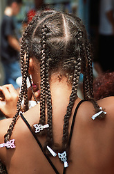 Rear view of young woman's head showing long tight plaits,