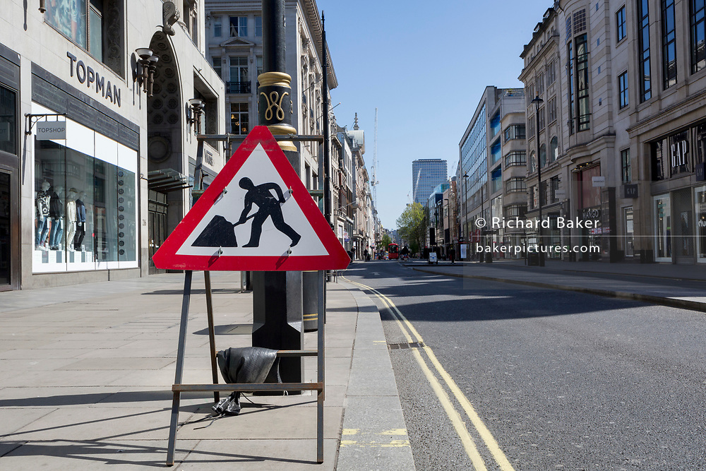 At the beginning of the fourth week of the UK government's lockdown during the Coronavirus pandemic, and with 120,067 UK reported cases with 16,060 deaths, a Men At Work traffic sign is on Oxford Street that would normally be a busy thoroughfare for shoppers and traffic and which remains largely deserted at mid-day, on 20th April 2020, in London, England.