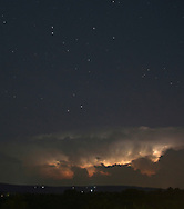 Middletown, New York -  Lightning from a distant thunderstorm lights up clouds on the horizon as star shine above in the night sky on July 17, 2010.
