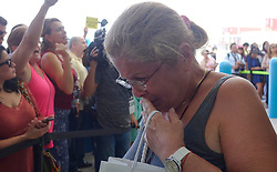A Caribbean hurricane evacuee who arrived on board the Royal Caribbean Adventure of the Seas, reacts to the cheers of waiting crowds Tuesday, Oct. 3, 2017, at Port Everglades in Fort Lauderdale. More than 3,000 people from Puerto Rico and the U.S. Virgin Islands were brought to Florida on board the Royal Caribbean Adventure of the Seas, Tuesday, Oct. 3, 2017, at Port Everglades in Fort Lauderdale. Photo by Joe Cavaretta/Sun Sentinel/TNS/ABACAPRESS.COM