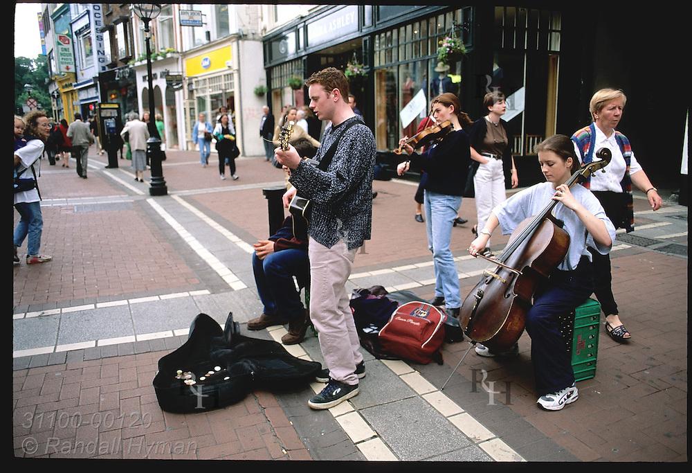 Pedestrians pass street musicians on Grafton Street, posh walking mall in downtown Dublin. Ireland