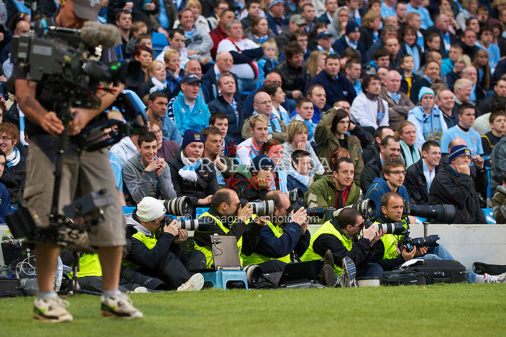 MANCHESTER, ENGLAND - Wednesday, May 5, 2010: Photographers sitting on the floor covering Manchester City versus Tottenham Hotspur during the Premiership match at City of Manchester Stadium. (Photo by David Rawcliffe/Propaganda)