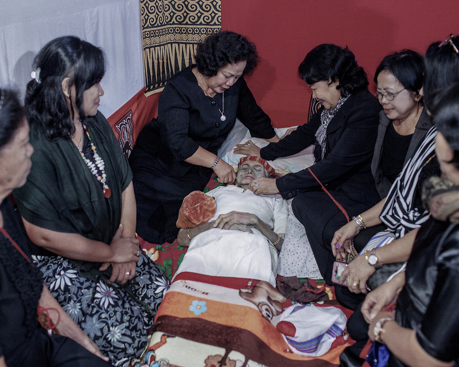 In Torajan culture, death is not necessarily the end.  The body of Lai' Tiku who passed on a few months ago is seen in her home.  She is surrounded by her personal belongings which will be placed inside her coffin while family members grieve next to her.  The matriarch in her family, Nenek Lai' Tiku passed away at age 102, she is survived by 10 children, 49 grandchildren, and 162 great-grandchildren.
