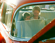 Riley Haugeberg, left, and Emma Citrowske, watch Frozen on an iPad while sitting in the 1956 Chevy Bel-Air of Emma's Dad, Ryan, during West Fargo Cruise Night on Sheyenne Street, Thursday, June 19, 2014.<br /> Nick Wagner / The Forum