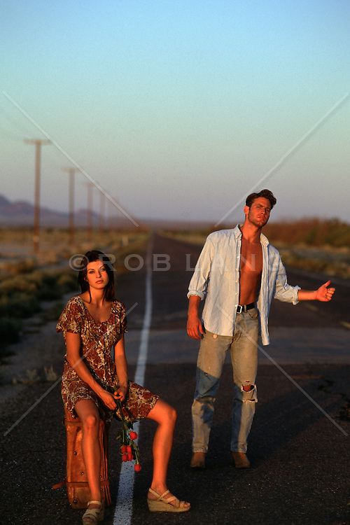 couple on a road in the desert hitchhiking