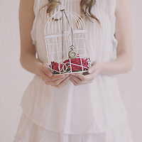 faceless portrait of a girl holding a white metal cage with red flowers and a watch
