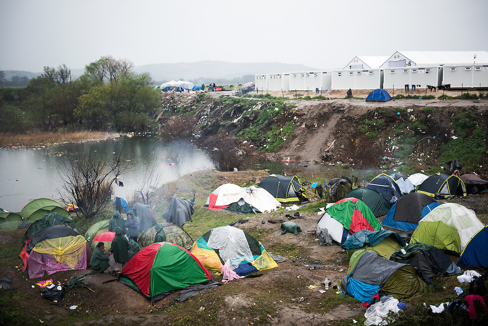 Tents in a flooded trench between the border and the  transit camp of Idomeni, Greece. <br /> <br /> Thousands of refugees are stranded in Idomeni unable to cross the border. The facilities here are stretched to the limit and the conditions are appalling. It's raining, it's cold there is mud everywhere and there is no hope that the border will open anytime soon.