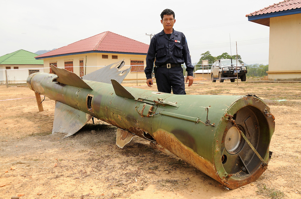 "Phet Senthavisouk, from Mines Advisory Group, stands next to a Russian Surface To Air Missle (SAM) that killed several villagers who found it in the forest.  The majority of deaths caused by unexploded ordinance (UXO) in Laos now are due to people intentionally contacting the weapons to sell for scrap metal.  ..Laos was part of a ""Secret War"", waged within its borders primarily by the USA and North Vietnam.  Many left over weapons supplied by China and Russia continue to kill.  However, between 90 and 270 million fist size cluster bombs were dropped on Laos by the USA, with a failure rate up to 30%.  Millions of live cluster bombs still contaminate large areas of Laos causing death and injury.  The US Military dropped approximately 2 million tons of bombs on Laos making it, per capita, the most heavily bombed country in the world. ..The women of Mines Advisory Group (MAG) work everyday under dangerous conditions removing unexploded ordinance (UXO) from fields and villages...***All photographs of MAG's work must include (either on the photo or right next to it) the credit as follows:  Mine clearance by MAG (Reg. charity)***."