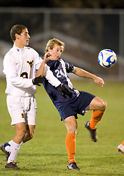 Virginia defender Matt Williams (24) kicks the ball despite being held by West Virginia forward Paul Paradise (9).  The West Virginia Mountaineers defeated the Virginia Cavaliers 1-0 in the second round of the 2007 NCAA Men's Soccer Tournament at Dick Dlesk Stadium in Morgantown, WV on November 28, 2007.