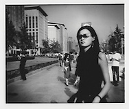 A new attitude.  Fashionable young woman fires off a wilting gaze out from behind designer sunglasses, Beijing, China.  A new generation, fortified with disposable income, has come of age.