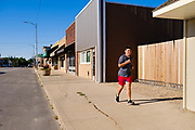 "03 AUGUST 2020 - JEWELL, IOWA:  A person jogs down Main Street in Jewell Monday morning. The only grocery store in Jewell, a small community in central Iowa, closed in 2019. It served four communities within a 20 mile radius of Jewell. Some of the town's residents created a cooperative to reopen the store. They sold shares to the co-op and  held fundraisers through the spring. Organizers raised about $225,000 and bought the store, which had its ""soft opening"" July 8. The store celebrated its official reopening Monday August 3. Before the reopening, Jewell had been a ""food desert"" for seven months. The USDA defines rural food deserts as having at least 500 people in a census tract living 10 miles from a large grocery store or supermarket. There is a convenience store in Jewell, but it sells mostly heavily processed, unhealthy snack foods that are high in fat, sugar, and salt.         PHOTO BY JACK KURTZ"