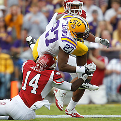 November 25, 2011; Baton Rouge, LA, USA;  LSU Tigers running back Kenny Hilliard (27) is tackled by Arkansas Razorbacks safety Eric Bennett (14) during the first quarter of a game at Tiger Stadium.  Mandatory Credit: Derick E. Hingle-US PRESSWIRE