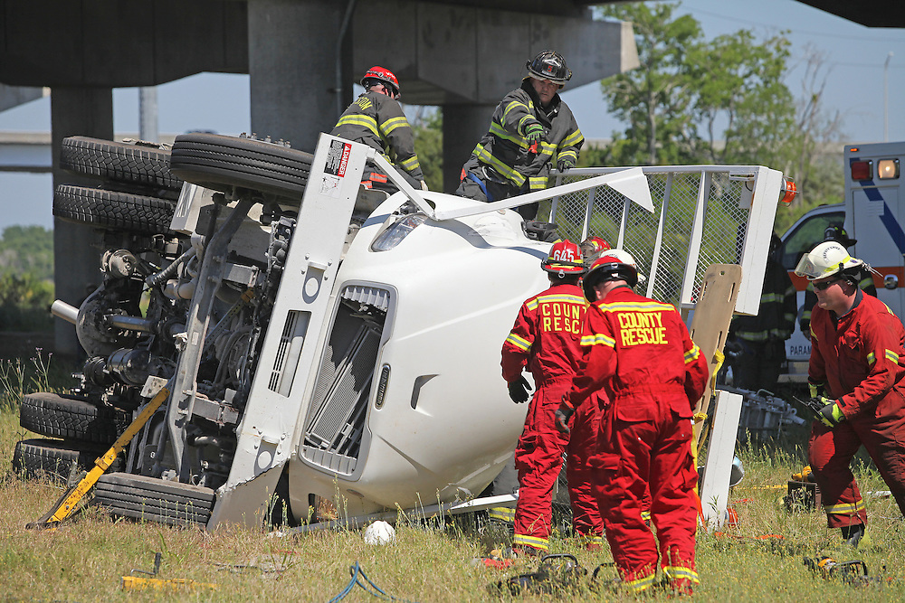 ANDREW KNAPP/STAFF -- May 15, 2013 -- Rescue workers and firefighters work Wednesday afternoon to free the occupants of a Sumter Utilities truck that plunged off northbound U.S. Highway 17 near the Meeting Street exit in downtown Charleston.
