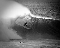 A surfer takes a wave at Uluwatu, Bali, Indonesia.
