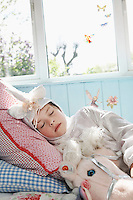 Young girl (5-6) in unicorn costume sleeping on bed with toy horse