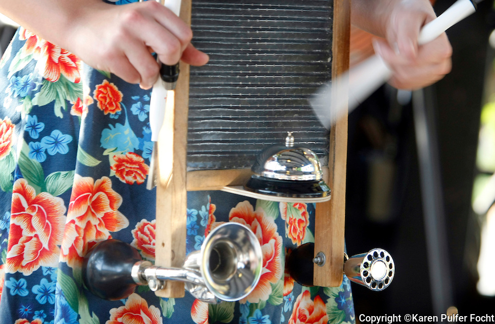 June 19, 2014 – Many of the instruments used in authentic, vintage music were home made or simple instruments, such as a washboard, bell, horn, thimble, broom handle or wash bucket.  The band has made some of their own instruments, like this washboard played by Mandy Martin.