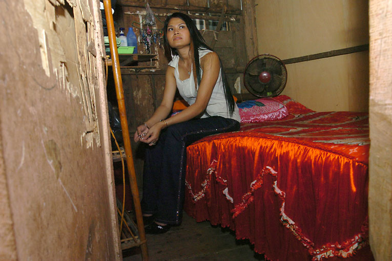 Cambodia.  Phnom Penh. 2006. Somaya (changed name), a sex worker in her tiny shack like room inside a brothel. Somaya is young and beautiful and does not work with regular clients, she only resides in the brothel; she works in high class bars and clubs with foreign clients. Somaya earns five to six hundred US dollars a month, equivalent to a good salary in Phnom Penh; she uses the money to support her family and relatives in her rural home village.