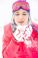Young woman wearing winter coat blowing snow outdoors