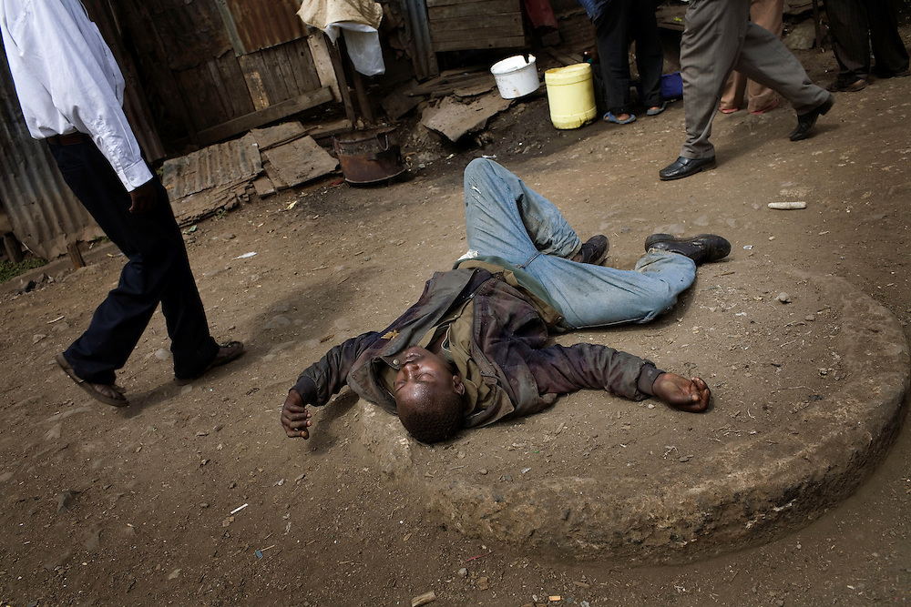 A drunk man passes out in the streets of Mathare, one of the poorest slums in Nairobi.  Running water and electricity are scarce and trash and human waste fills the streets.  Many people have no jobs and those who do work can earn less than one dollar a day.