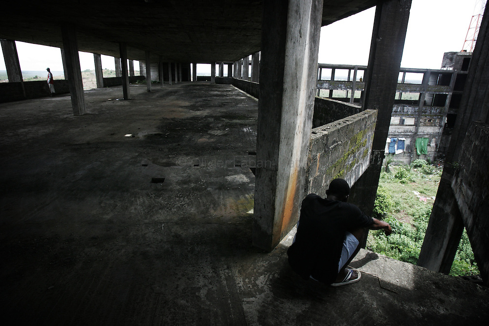 """A man sits 19 September 2005 on one of the many levels of the former uncompleted Ministry of National Defense building in Congo Town on the outskirts of Monrovia. The """"Pentagon"""", named this way by its occupants, shelters 394 families totalling approximately 3,000 people who were booted out in May 2005 of the Barclay Training Center, which had been their home for the last two decades. Former soldiers, who fought for former Liberian presidents Samuel Doe and Charles Taylor, live in this building with no water or electricity, overcoming past differences. The construction of the building started in 1984 under Doe's leadership, and the war interrupted the its completion and later served as a base for Taylor's men."""