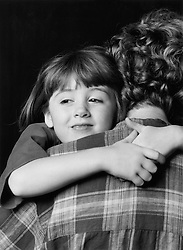 Young girl hugging woman; with arms around her neck; smiling,