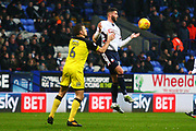 Bolton's Gary Madine chests the ball under pressure from Burton Albion's Ben Turner during the EFL Sky Bet Championship match between Bolton Wanderers and Burton Albion at the Macron Stadium, Bolton, England on 16 December 2017. Photo by John Potts.