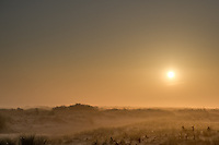 A wide angle view of a sunrise, as seen on a Autumn morning from Schiermonnnikoog island, the Netherlands.